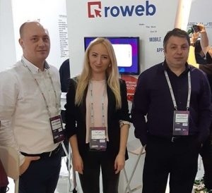 3 people standing in front of Roweb stand